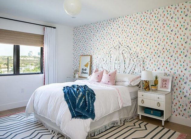 boho girls room with white rattan bed and polka dot wallpaper