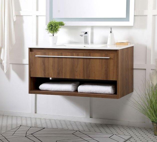 wood floating bathroom vanity in bathroom space with white wall