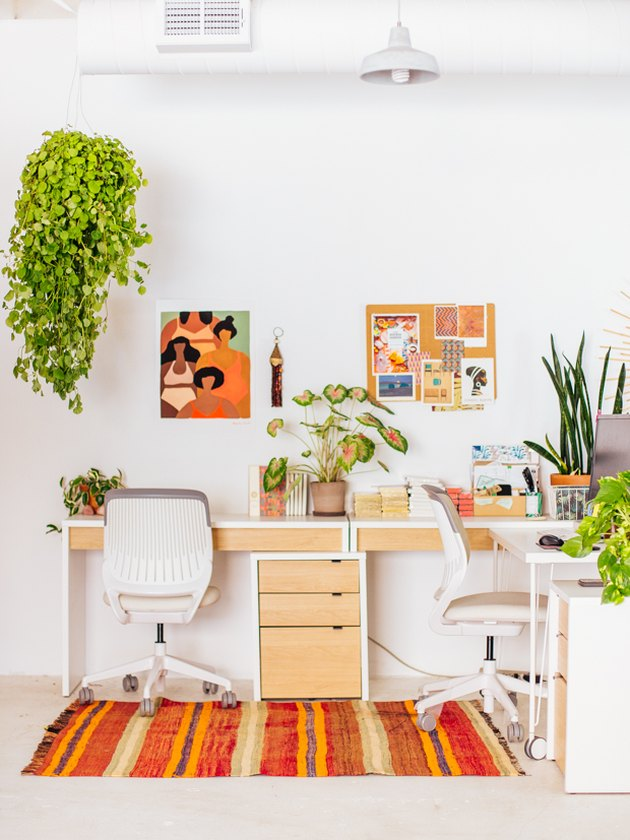 Boho office with warm colors, abstract artwork, and plants