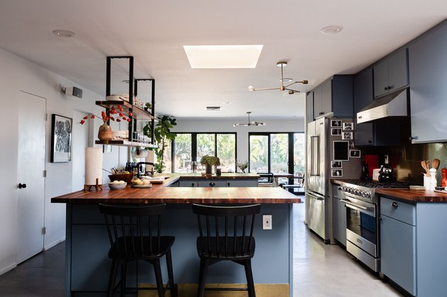 kitchen with blue cabinetry, wood countertops, hanging shelves
