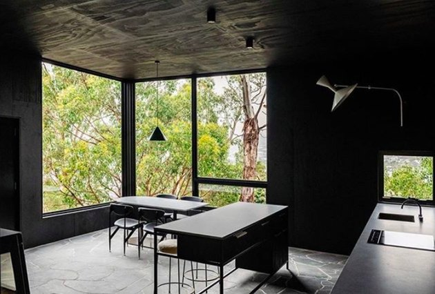moody design with dark kitchen floors made of large stone slab and contrasting grout and black walls