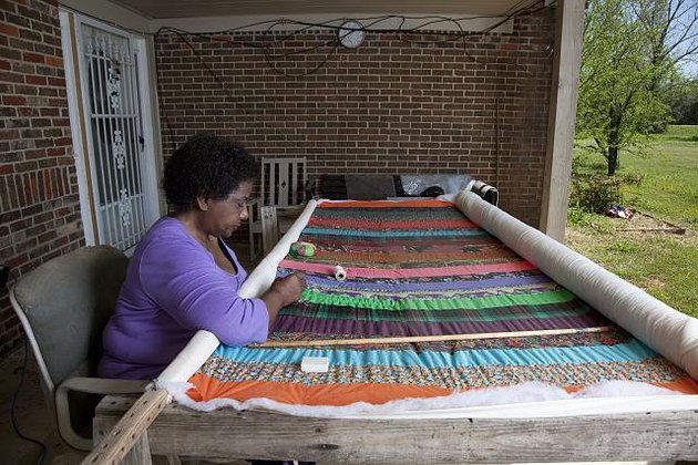 woman sitting in front of quilt she is working on