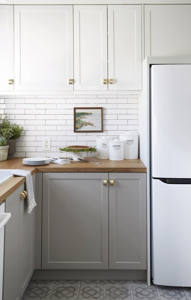 lower gray kitchen cabinets with upper white cabinets