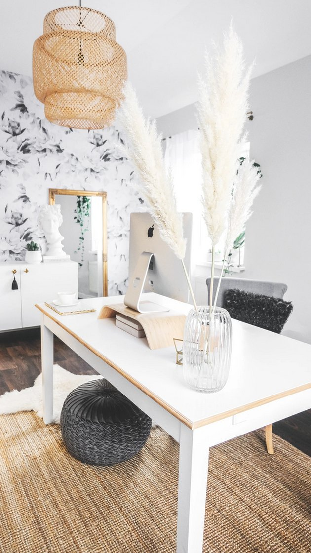 Boho office with pampas grass, white desk, and bamboo chandelier