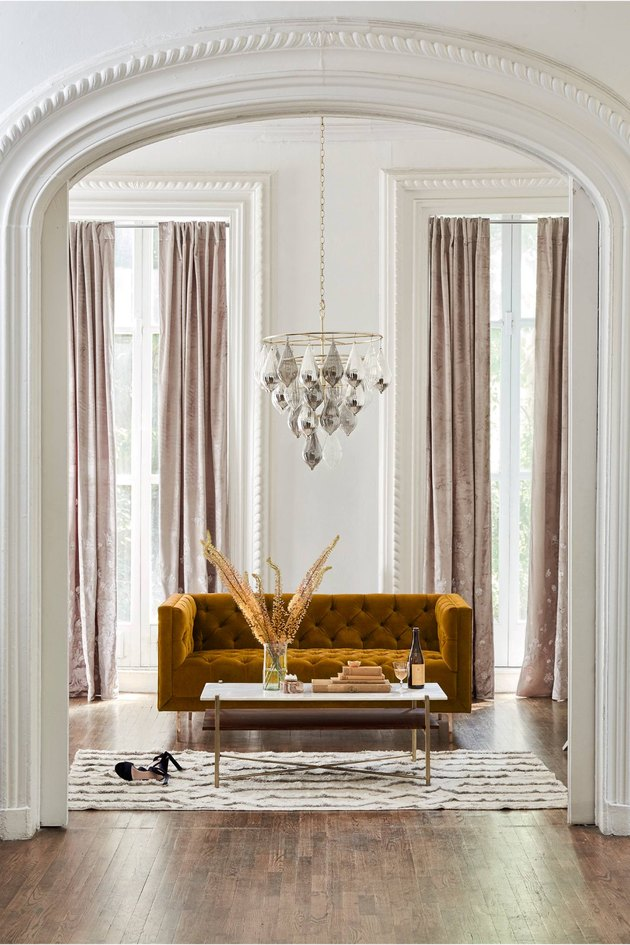 elegant art deco living room with mustard sofa and large droplet chandelier