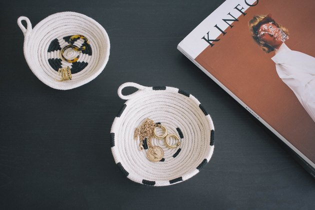 Two DIY painted cotton rope bowls on table with jewelry inside