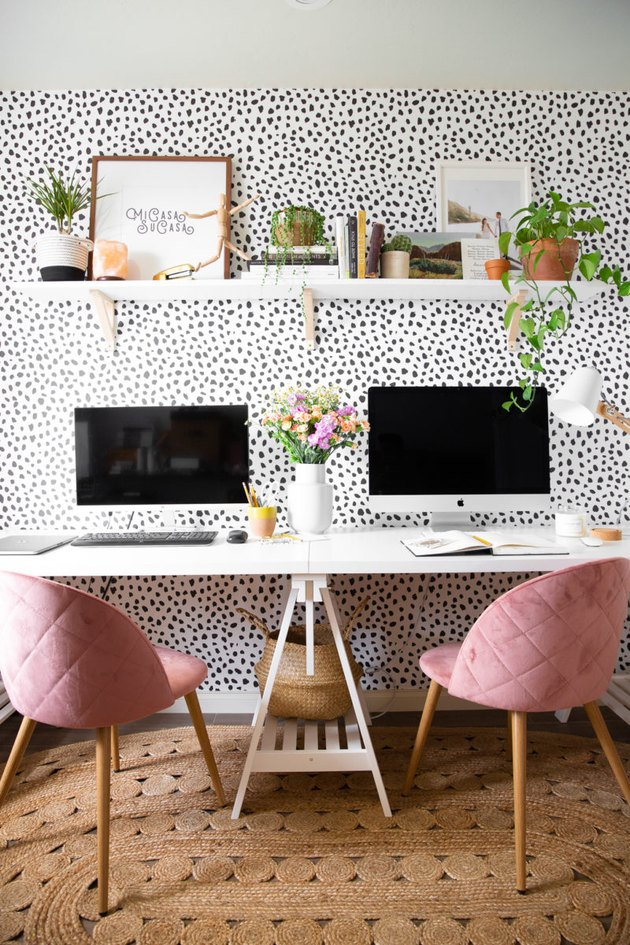 Boho office with black and white polka dot wallpaper and pink chairs