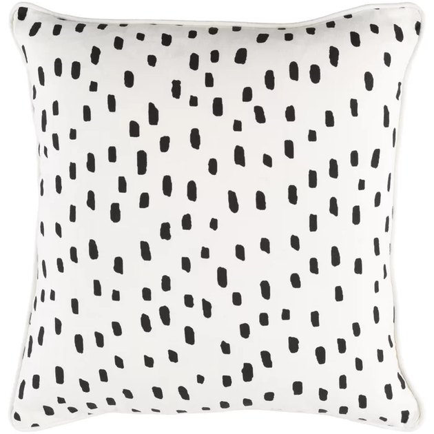 White square throw pillow with small black polka dots in various sizes