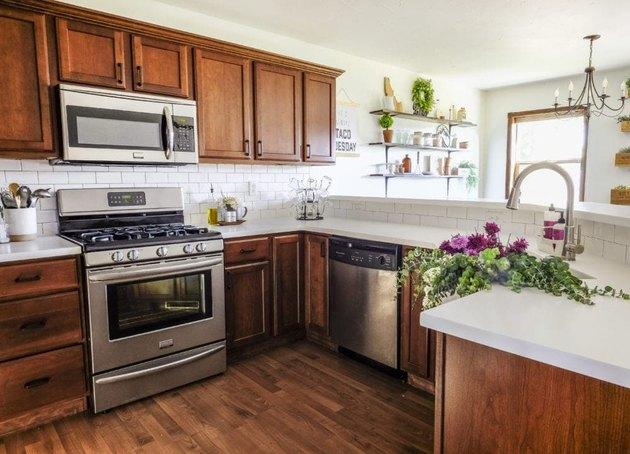 Walnut craftsman kitchen cabinets with matching wood floor and white subway tile backsplash