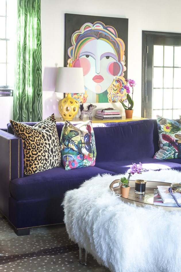 Hollywood Regency living room with purple velvet couch and abstract artwork