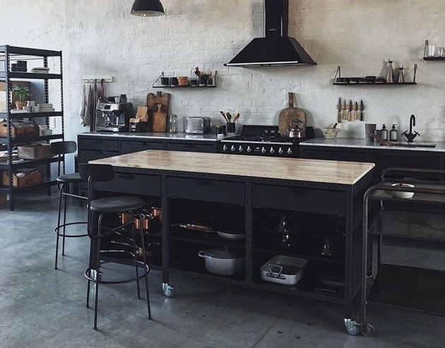 black wooden industrial kitchen island with glossy butcher block top and metal barstools
