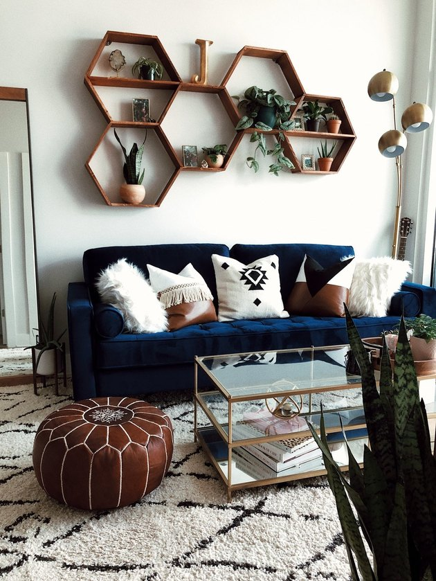 Boho apartment decor with navy blue couch, geometric shelving, and leather pouf in living room
