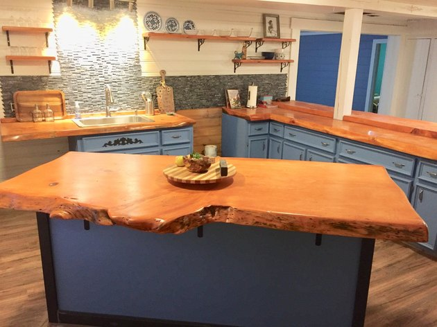 Live-edge wood slab in contemporary kitchen with blue cabinetry and wood floors