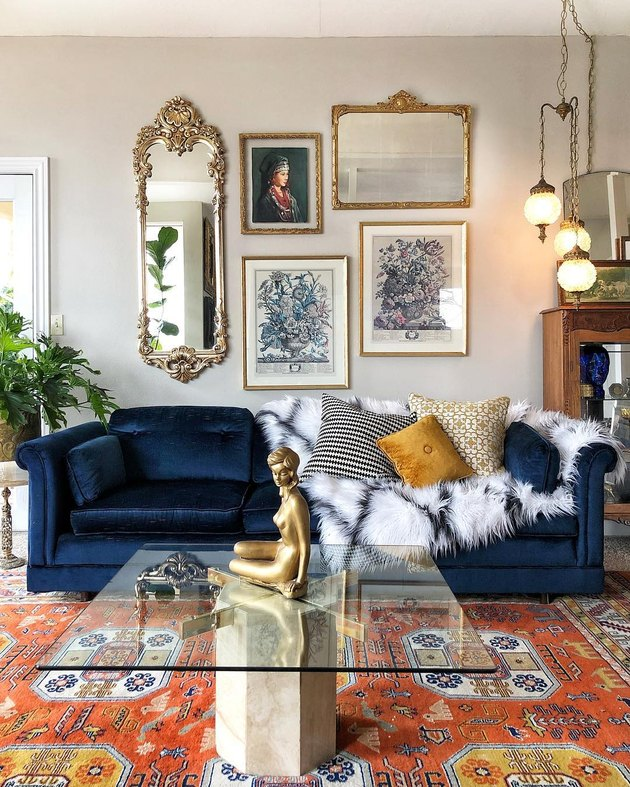 Hollywood Regency living room with gallery wall and blue velvet couch