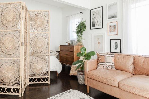 Bohemian apartment with rattan room divider and leather couch