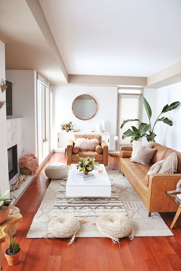 Boho apartment decor in living room with leather furniture and woven floor cushions
