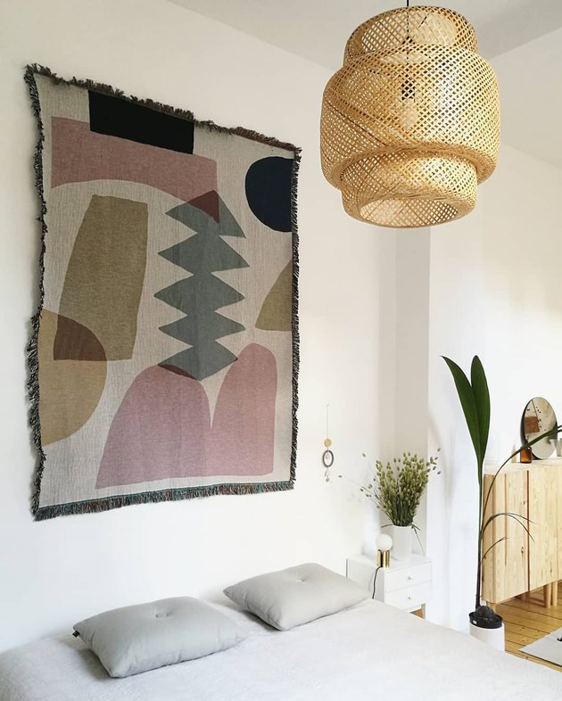 Boho apartment decor in bedroom with geometric tapestry and bamboo pendant light