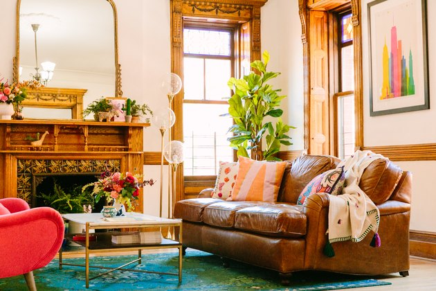 Boho apartment decor in living room with leather couch, wood fireplace, and midcentury floor lamp
