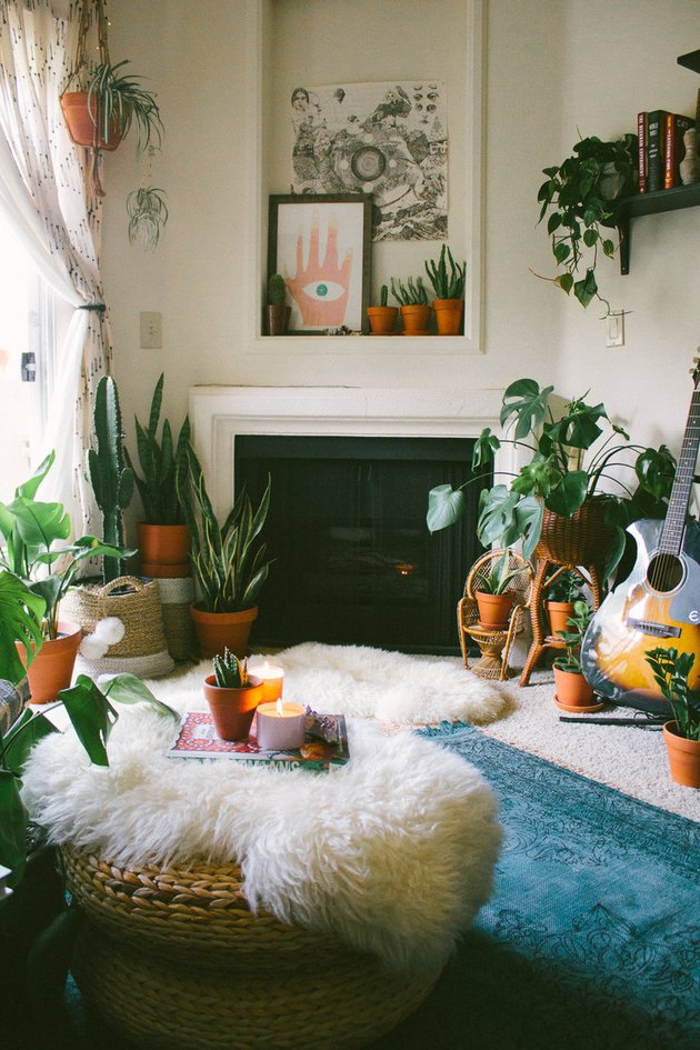 Boho apartment decor in living room with faux fur rugs, plants, and abstract artwork
