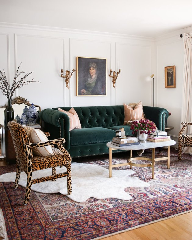 Hollywood Regency living room with green velvet couch and leopard print chairs