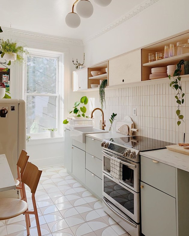 Boho apartment decor in galley kitchen with geometric floor tile and light green cabinets