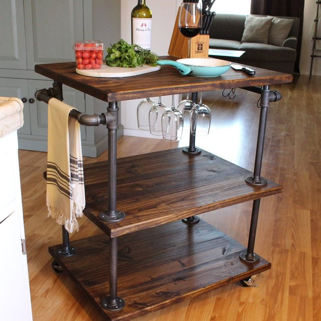 Three-tier industrial bar cart with pipes and hanging wine glasses and casters