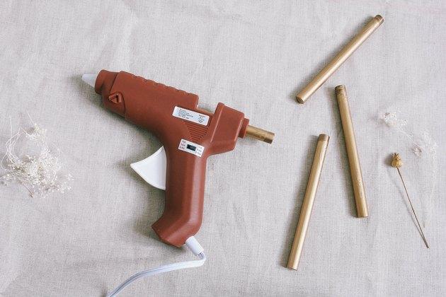 Three gold sealing wax sticks next to glue gun loaded with wax stick