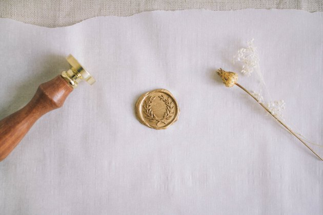 Finished gold wax seal cooling on parchment paper