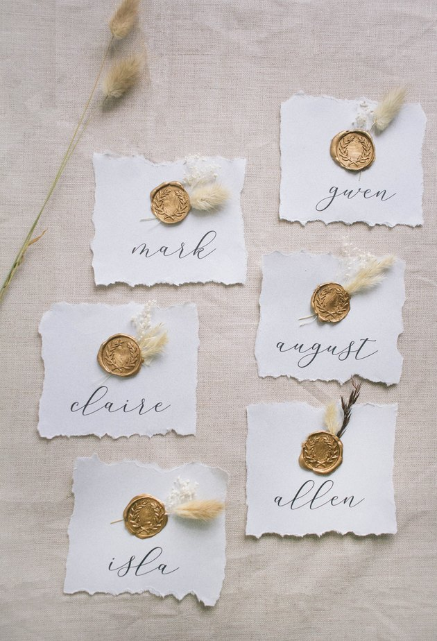 Six DIY gold wax seal place cards with dried flowers