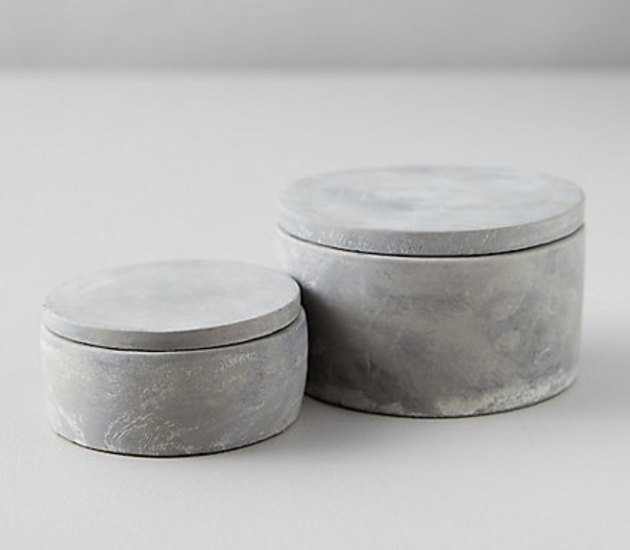 Two cement jars with lids in two sizes.