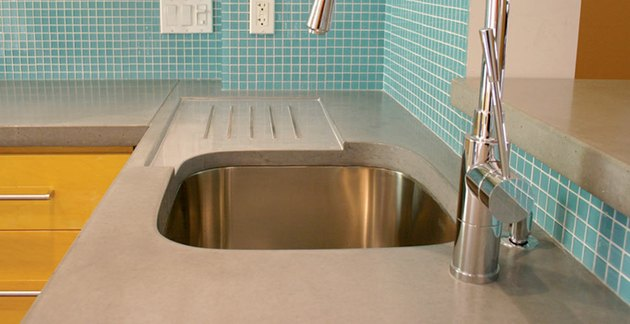 Concrete kitchen countertop with embedded drainboard and teal tile backsplash