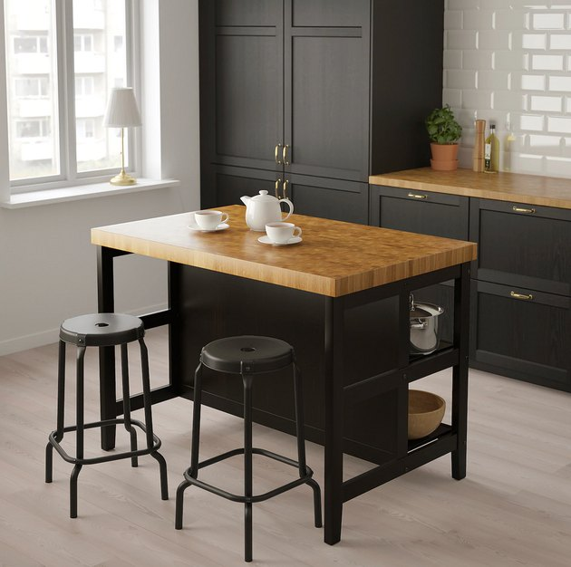 Black and oak IKEA kitchen island in modern kitchen with black cabinets