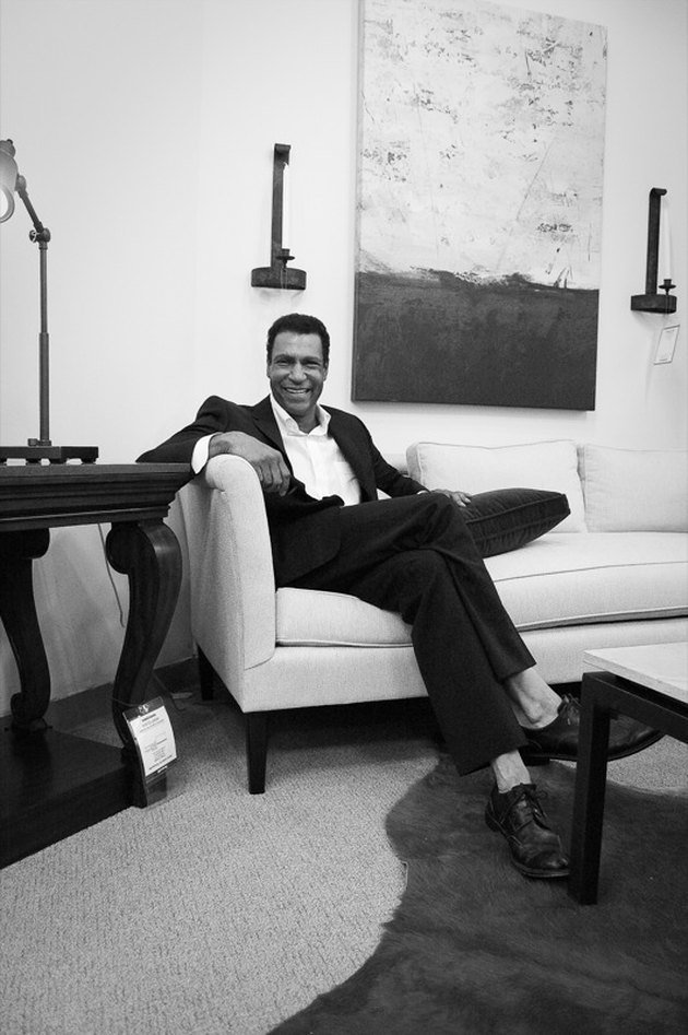 black and white photograph of designer darryl carter sitting on a couch