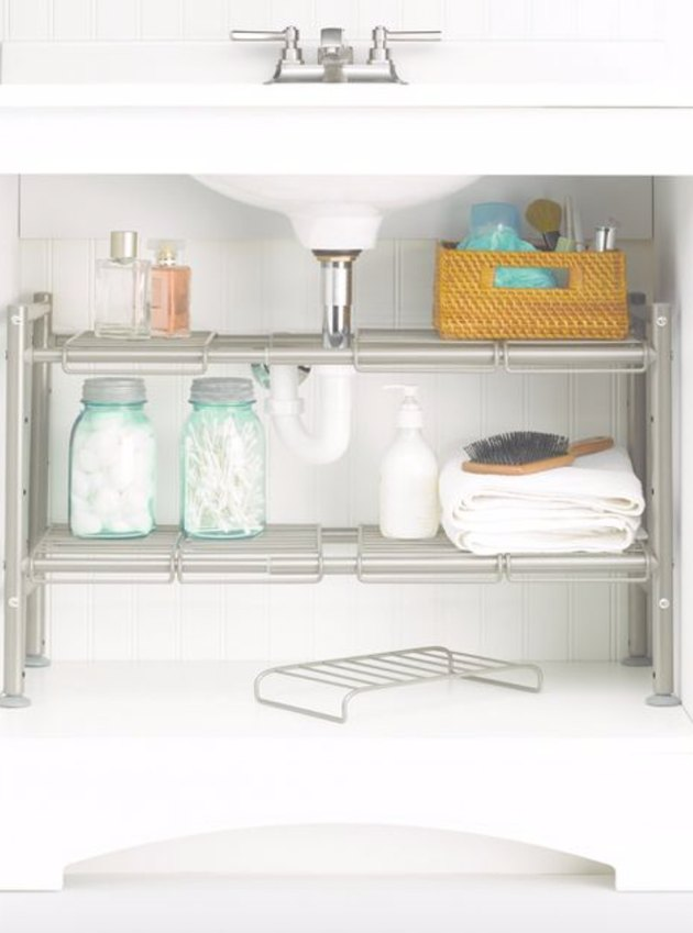 Two adjustable metal shelves underneath sink.