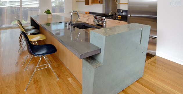 Tricolored concrete island in modern kitchen with wood floors and Eames chairs