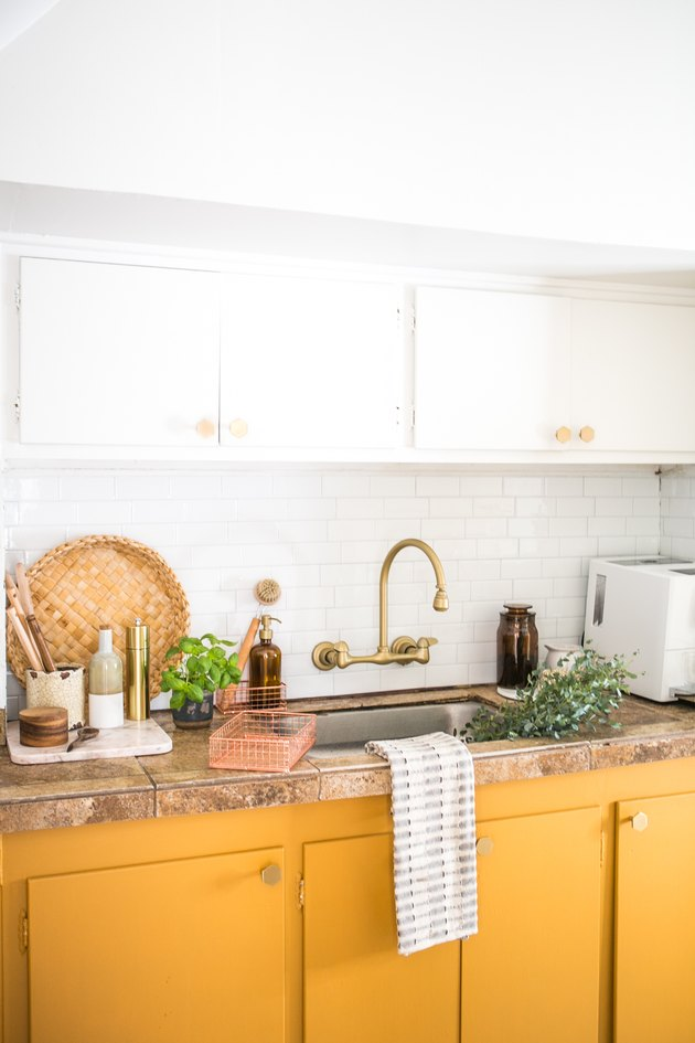 kitchen space with white and mustard cabinets and gold sink faucet