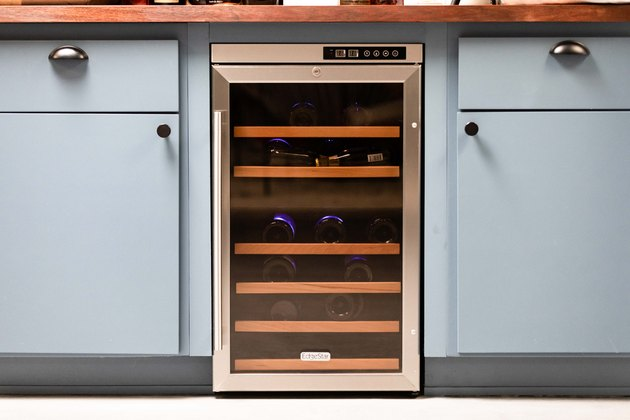 close up of wine fridge, blue kitchen cabinetry and modern kitchen knobs