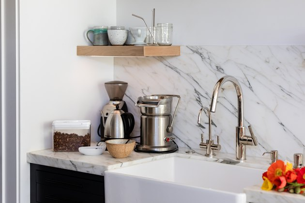 kitchen faucet with natural stone backsplash and farmhouse sink