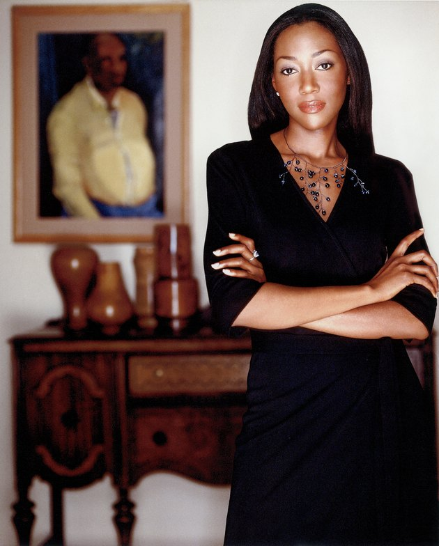 photograph of designer keita turner standing in interior featuring a painting and wood dresser