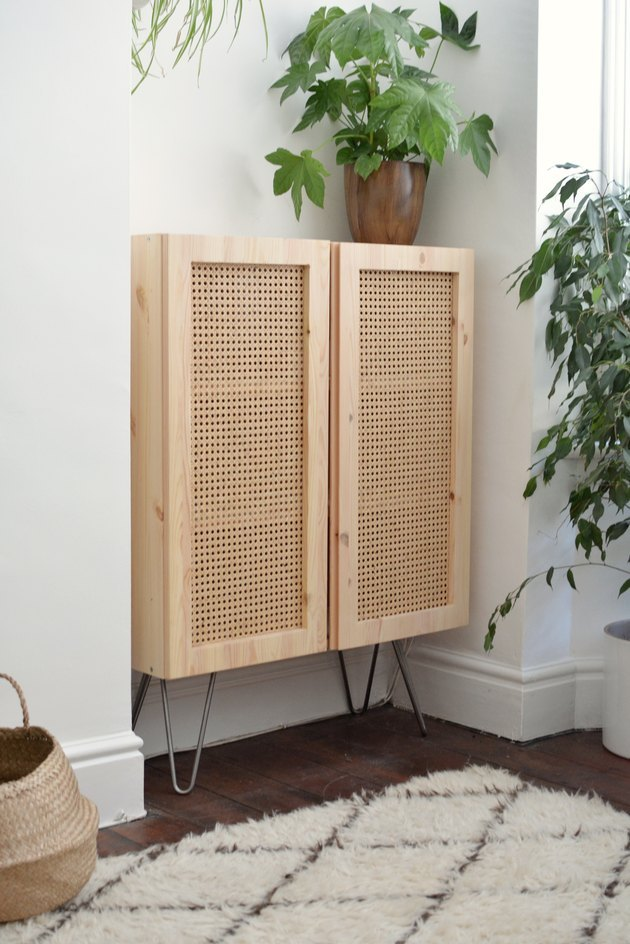 Wood cabinet with cane doors, with fuzzy white and black rug and plants.