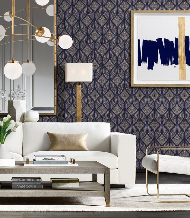 living room in art deco style with dark patterned wallpaper and white couch