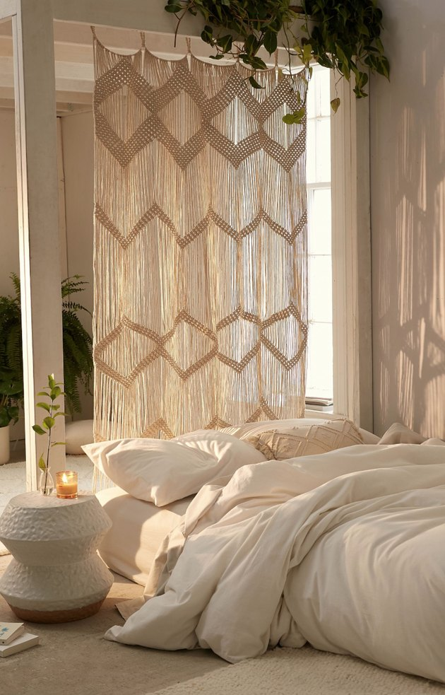 Macrame curtain in natural hanging in bedroom.