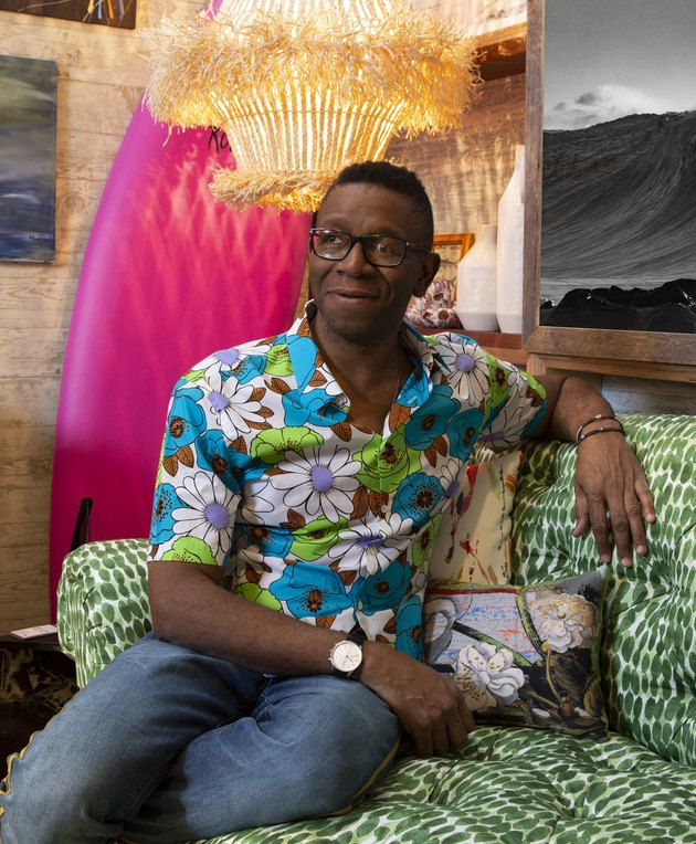 photograph of designer rayman boozer reclining on green patterned couch