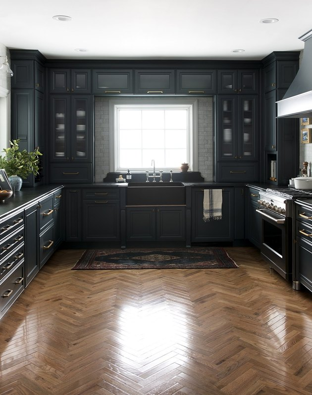 Hardwood herringbone modern kitchen flooring with navy blue cabinets