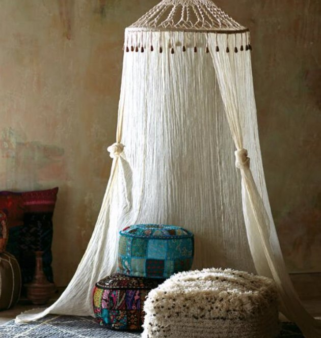 Gauze and macrame canopy hung from ceiling with floor pillows.