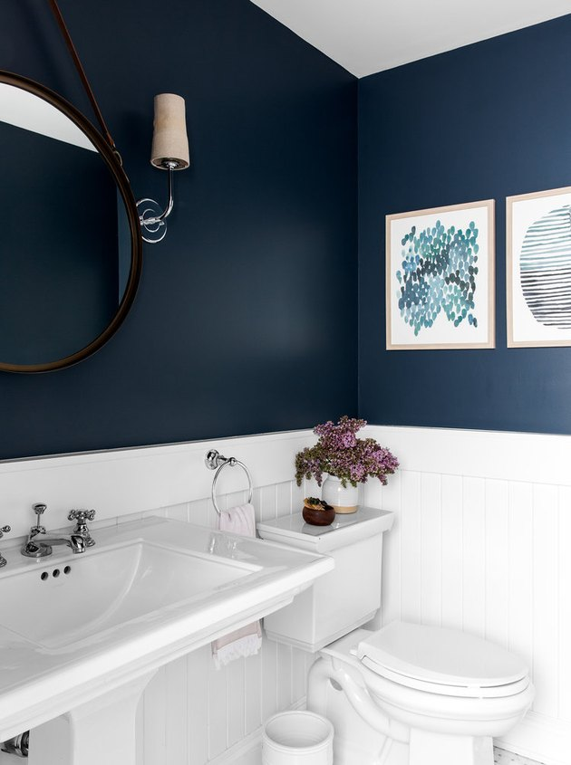 navy powder room with paintings and wood paneling