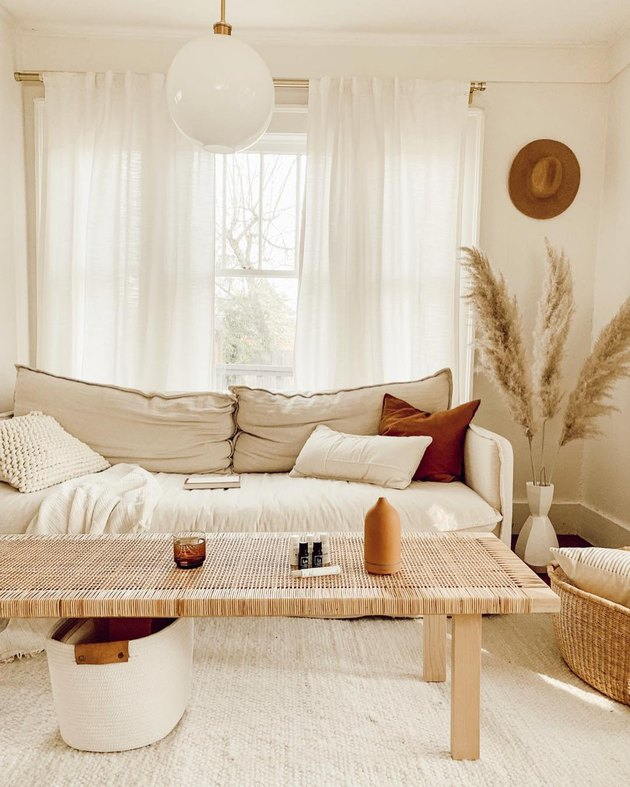 natural decor in cream-colored living room with linen sofa and woven coffee table