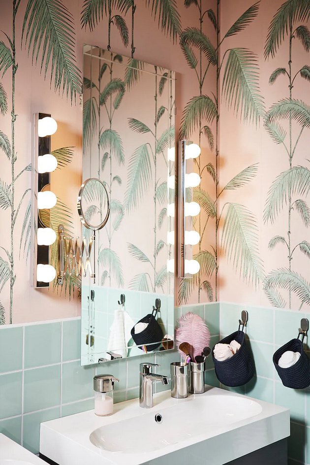 IKEA bathroom lighting idea with wall sconces next to mirror and palm leaf wallpaper