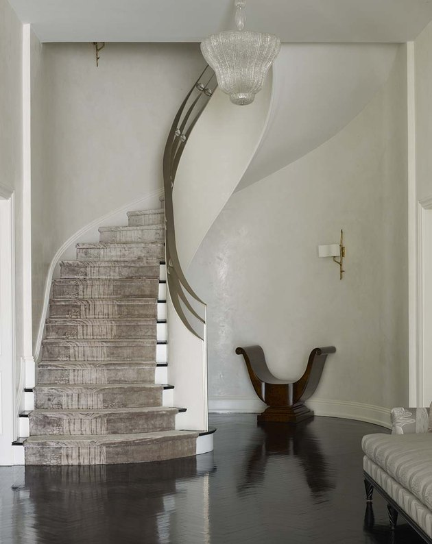 art deco staircase with brass railings and velvet carpet