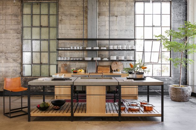 concrete industrial kitchen island with wooden shelf and metal legs in loft apartment